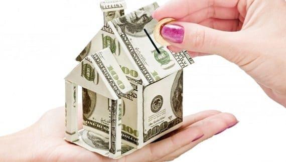 Mãos segurando uma casinha feita com uma cédula de dinheiro