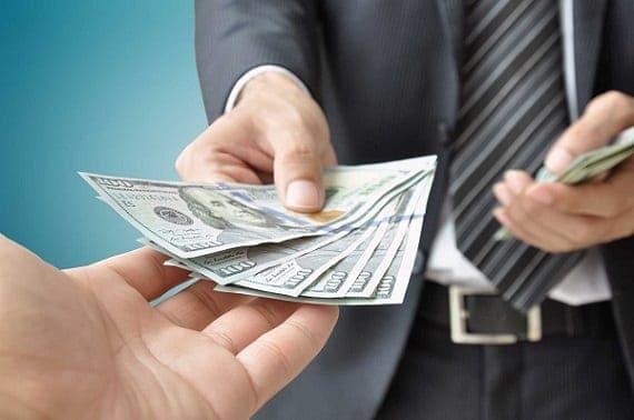 Homem dando cédulas de dólar para outro