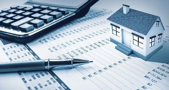 Calculadora, caneta e uma casa em miniatura sobre papel com números