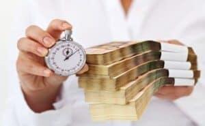 Mulher segurando várias cédulas e um relógio para simbolizar o tema fintechs de empréstimo