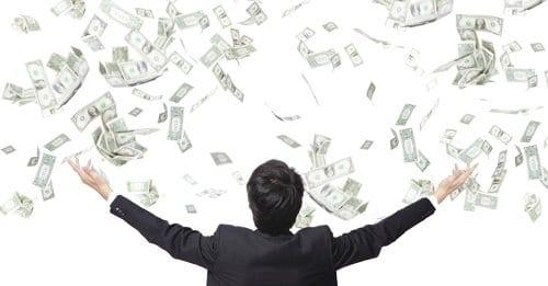 Homem e várias cédulas caindo sobre ele representando hábitos dos milionários