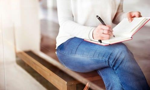 Mulher sentada em um banco escrevendo suas metas em uma agenda