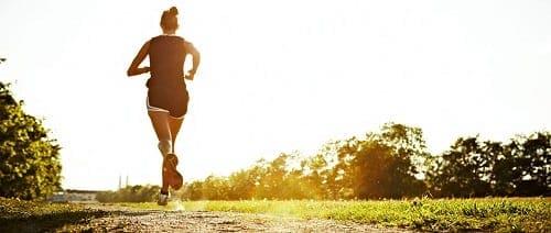 Mulher correndo em uma trilha
