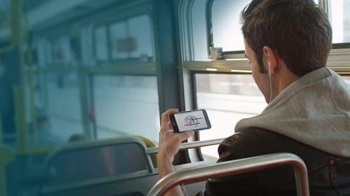 Homem vendo o celular enquanto está no ônibus