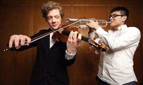 Homem tocando violino e outro tocando trompete