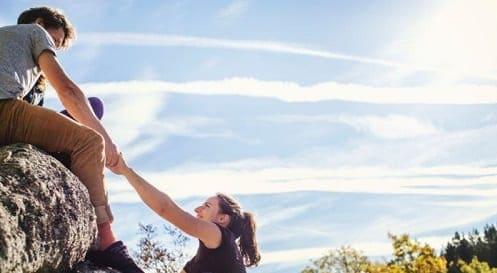 Homem puxando mulher para topo de uma colina