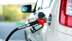 Bomba de combustível no tanque do carro simbolizando o tema Gasolina ou álcool