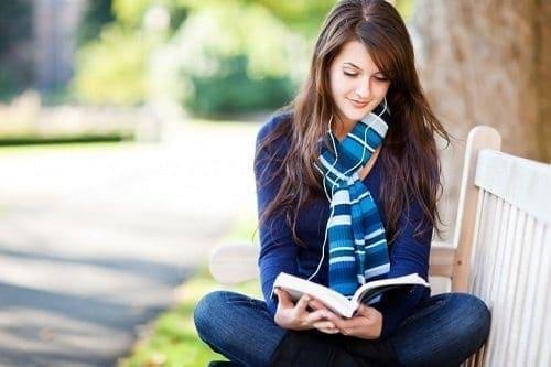 Moça lendo livro no parque tentando aprender mais sobre educação financeira