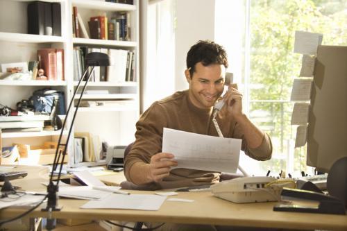 Homem trabalhando em casa e vendo dicas sobre como se manter produtivo