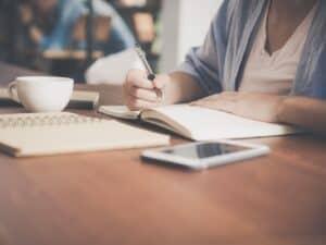 Imagem de uma mulher sentada em uma mesa com um caderno, caneta, um copo de café e seu celular, em um ambiente de estudo. Usamos a foto para ilustrar o nosso conteúdo sobre o cartão PoupCard Bradesco.