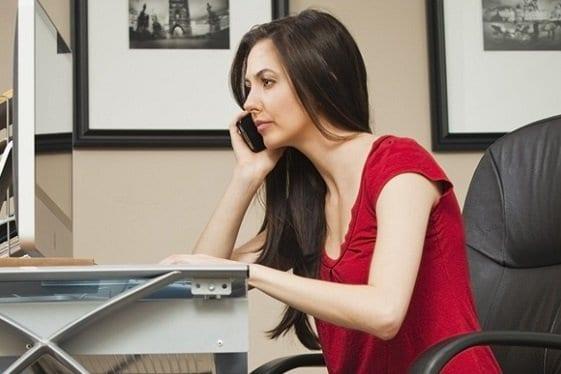 Mulher ao celular e usando notebook para pesquisar ideias de negócios