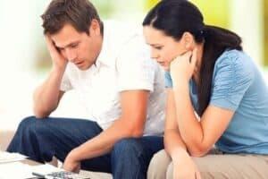Casal olhando pras dívidas e pensando Como superar a crise econômica