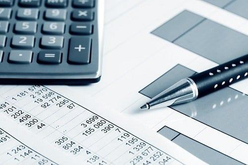 Caneta, gráficos e calculadora simbolizando metas e orçamentos