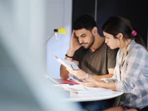 Imagem de um casal sentado em um escritório com vários papéis e canetas em uma mesa, analisando documentos. Usamos a imagem para simbolizar nosso post sobre cartão de crédito para autônomo