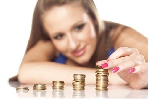 Mulher empilhando moedas e pensando como economizar dinheiro