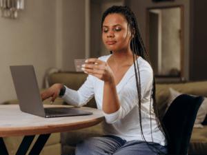 Imagem de uma mulher segurando um cartão de crédito e usando um notebook para ler algo na tela. Usamos a foto para ilustrar nosso post sobre crédito rotativo