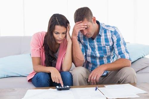 Casal com calculadora, papel e caneta fazendo um diagnóstico financeiro