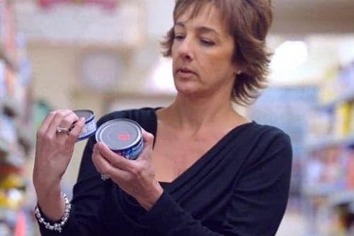 Mulher comparando o preço de dois produtos semelhantes