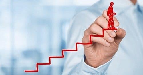 Mão desenhando uma escada com um homem no último degrau que ilustra a definição de objetivos do planejamento financeiro