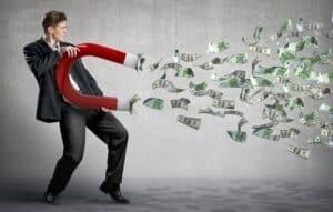 Homem com um imã atraindo dinheiro simbolizando o ato de conseguir o primeiro milhão antes dos 30 anos
