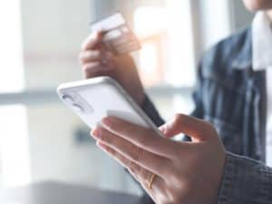 Imagem de uma pessoa segurando o celular e um cartão de crédito nas mãos, simbolizando o conteúdo que explica como proceder nos casos de cartão bloqueado