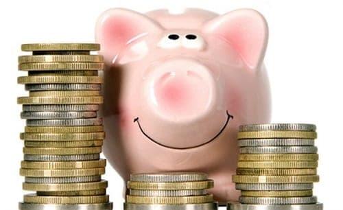 Cofrinho e pilhas de moedas simbolizando poupança