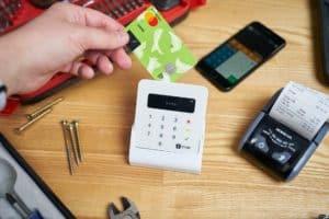 pessoa segurando cartão de crédito próximo a maquininha