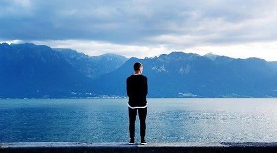 Milionário observando uma bela paisagem de montanhas e rio