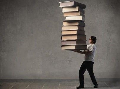 Homem carregando vários livros simbolizando aprendizado