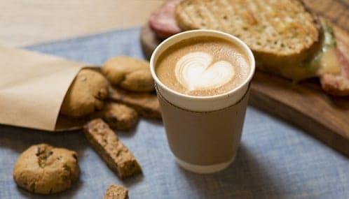 Copo com café, biscoitos e sanduíche