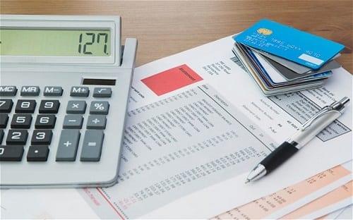 Calculadora, caneta, cartões de crédito e faturas de contas da casa