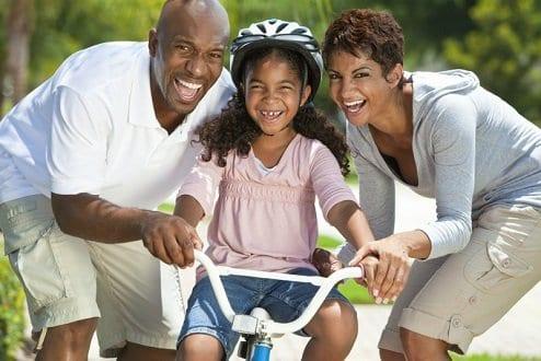 Casal ensinando a filha a andar de bicicleta simbolizando o tema Planejamento para ter um filho