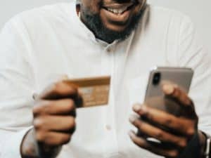 Imagem de uma pessoa usando um celular e um cartão de crédito. Usamos a foto para ilustrar o post sobre limite de crediário do cartão