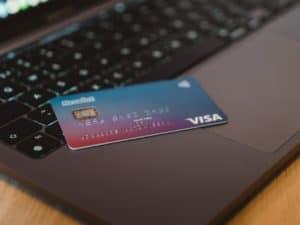 Imagem do teclado de um computador. Em cima dele, vemos um cartão de crédito nas cores azul e rosa. Imagem usada para ilustrar o post sobre o número BIN do cartão de crédito.