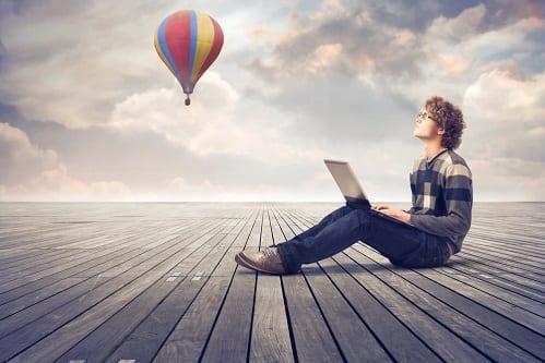 Jovem com notebook olhando para o céu
