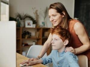 Imagem de uma mãe e um filho usando o computador em casa. Pais devem ficar atentos à cobrança indevida nas escolas
