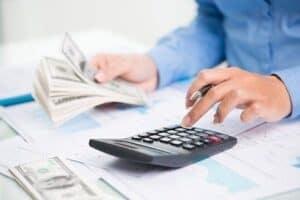 Homem com dólares e calculadora simbolizando o tema Cotação do dólar