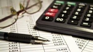 Óculos, calculadora, caneta e um papel para analisar despesas fixas e variáveis