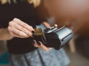 Imagem de uma mulher passando um cartão de crédito em uma máquina para simbolizar o post que fala sobre a diferença entre Gold e Platinum