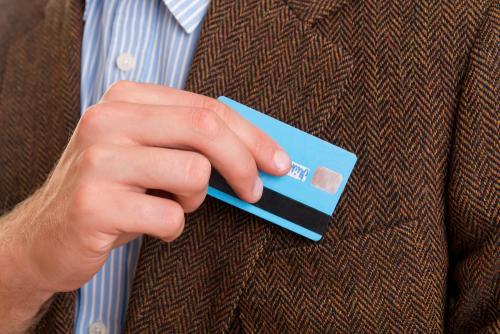 Homem colocando o cartão de crédito consignado no bolso do terno