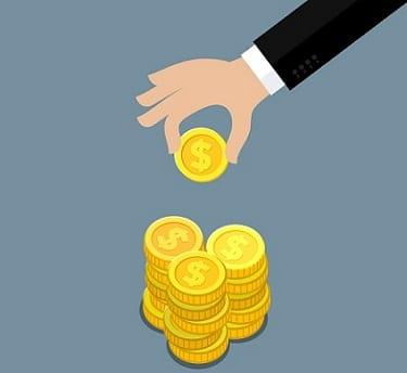 Mão colocando moedas em um cofrinho simbolizando como juntar dinheiro