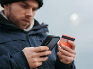 Imagem de um homem usando o cartão de crédito e seu celular para entender Como é feito o reembolso no cartão de crédito