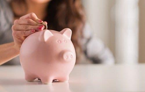 Mulher colocando dinheiro no cofrinho simbolizando o desafio 52 semanas para poupar dinheiro