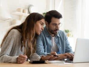 Imagem de um casal usando o computador e fazendo anotações. Imagem usada para ilustrar o post sobre parcelar a fatura do cartão CAIXA