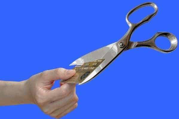 Cartão de crédito sendo cortado com uma tesoura simbolizando o tema Como sair das dívidas do cartão de crédito