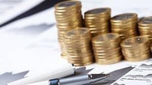 Várias moedas e caneta simbolizando como investir no Tesouro Direto