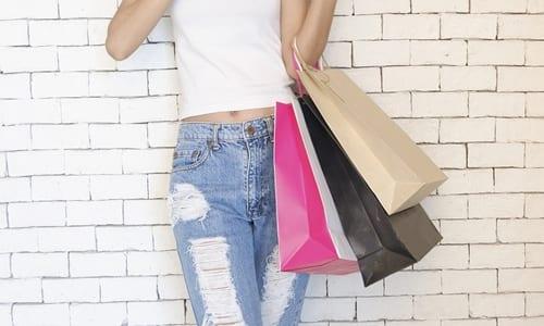 mulher com sacolas de compras no braço