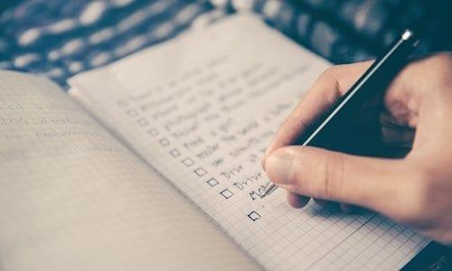 pessoa escrevendo uma lista em uma caderneta