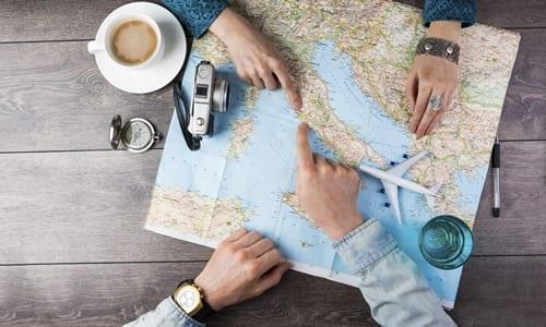 duas pessoas apontando para um mapa em cima da mesa