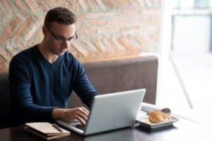 Homem usando notebook e pesquisando como saber se o seu nome está sujo